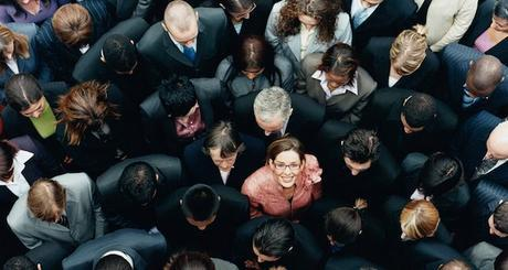 Businesswoman Looking up at Camera and Standing Outdoors Surrounded by a Large Group of Business People
