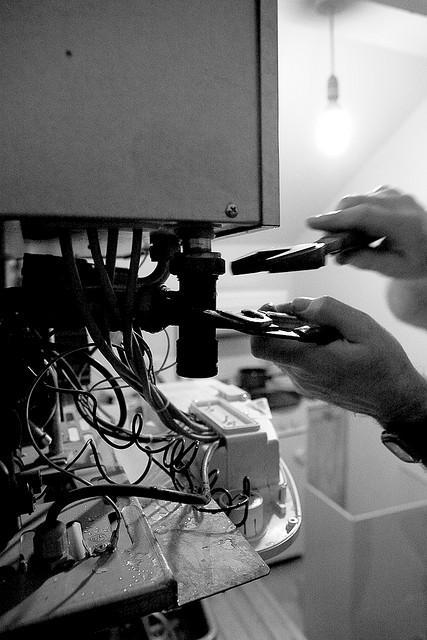An engineer fixing a boiler with a spanner and a wrench