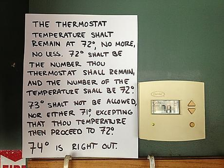 A note telling people to not turn the dial on a thermostat