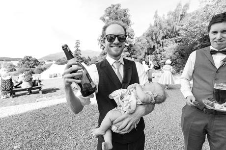 Dad holds baby and has a beer in other hand Derwentwater Independent Hostel Wedding