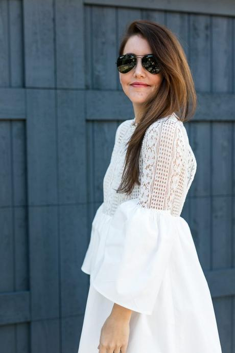 Amy Havins wears a white bell sleeve mini lace dress with stuart weitzman heels.