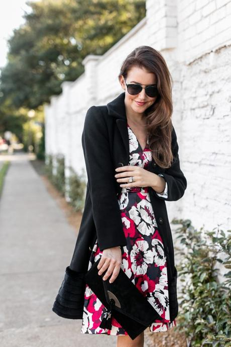 Amy Havins wears a flower dress and a black coat.