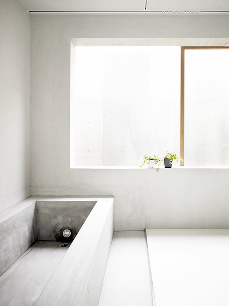 Minimalistic bathroom with concrete bathtub by Suppose Design Office
