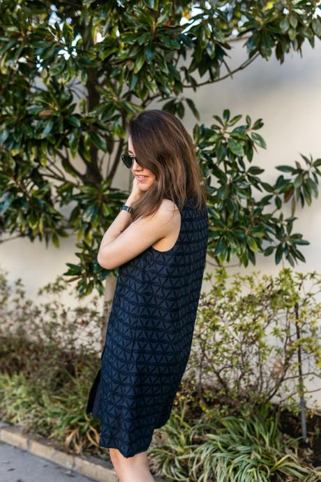 Amy havins wears a navy shift dress and spring sandals.