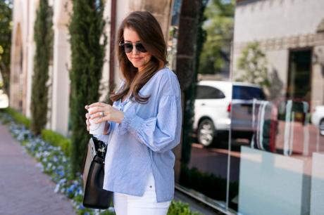 Amy havins wear a blue and white blouse with white jeans.