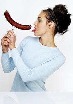 woman on a low carb diet licking a sausage