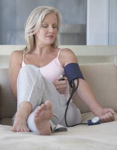 woman on a low carb diet checking blood pressure on sofa