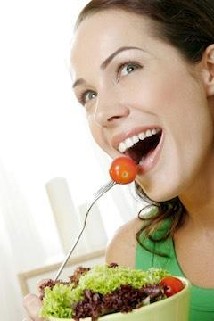 woman eating low carb salad and smiling