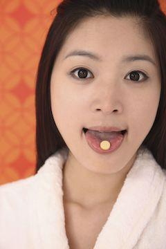 holding vitamin c tablet on tongue