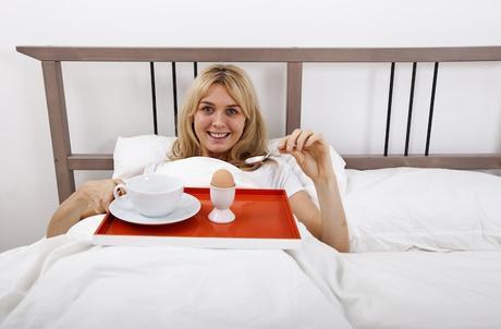 woman having egg breakfast in bed
