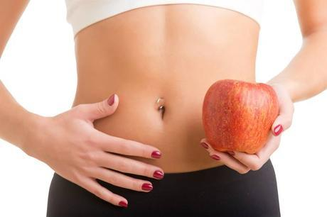 woman holding apple next to stomach
