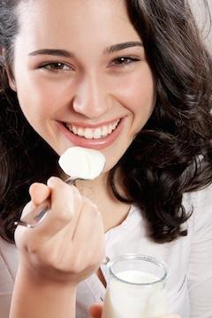 woman with spoon full of probiotic yogurt