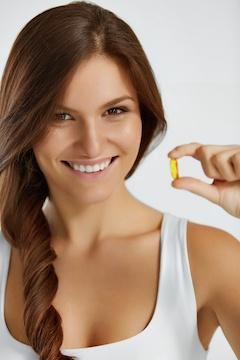 woman hold fish oil capsule