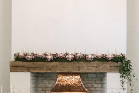 flowers over fireplace at blackwell grange wedding venue