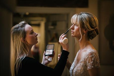 make up artist applying make up to bride