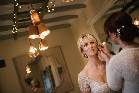 bride having ear rings adjusted on wedding day