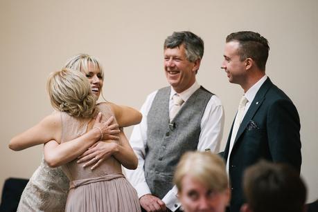 bride hugging bridesmaid, people laughing