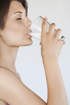 side view of woman drinking a glass of kefir