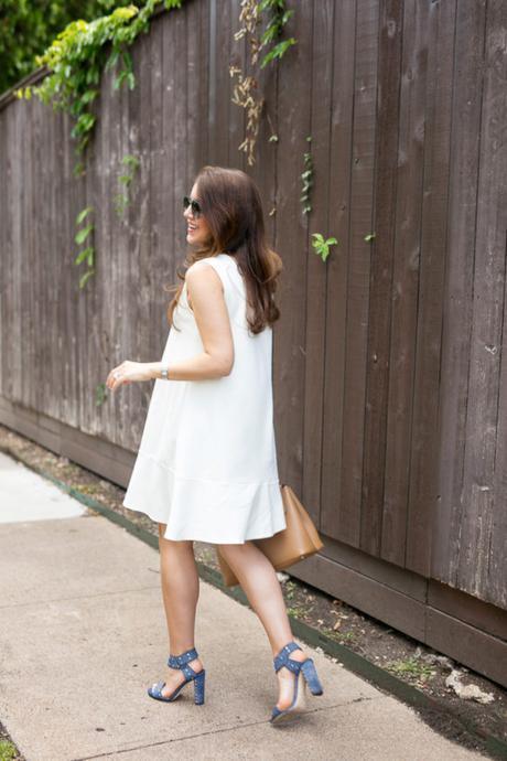 Amy Havins wears a white summer dress with blue jimmy choo heels.
