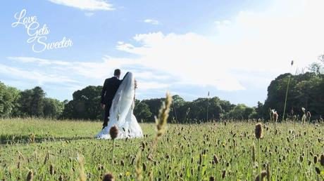 bride and groom take a stroll through the fields near the lake with her long cathedral length veil blowing in the wind