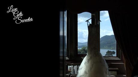 Pronovias fish tail lace wedding dress hanging in the window of Armathwaite Hall looking out to the lake district