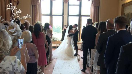 the bride and groom enjoy a kiss after being announced as husband and wife at armathwaite hall in the lakes