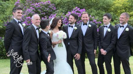 A bride and the groomsman having a fun wedding photo taken with the guys wearing classic black and white