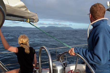 whale spout sailboat sailing ocean mountains