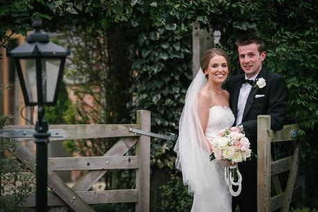 bride and groom standing by gate at mythe barn