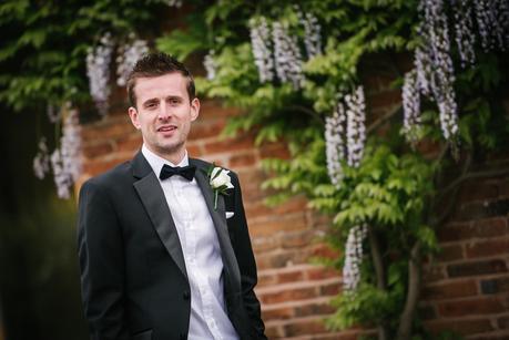 groom posing outside mythe barn