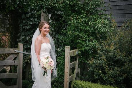 bride on her own outside mythe barn