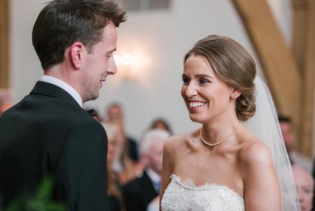 bride smiling at groom in mythe barn ceremony