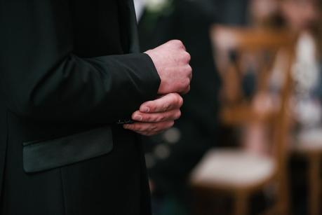 groom holding his cuff link