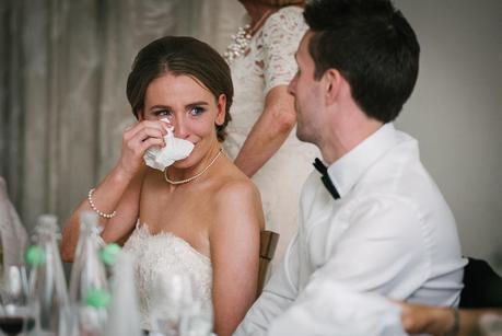 bride looking at groom wiping her eye