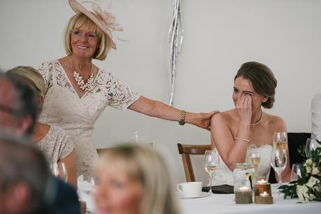 mother of the bride smiling and bride crying