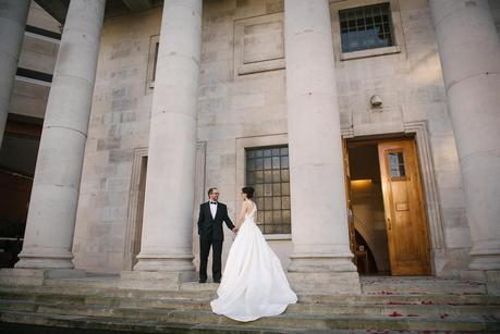 bride and groom posing outside a building with pillars