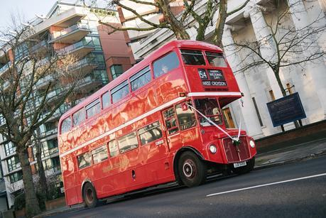 red london bus with wedding guests