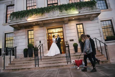 bride and groom posing, people walking dog