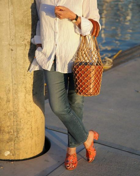 details: style blogger Susan B. wears Sam Edelman orange slide sandals and a Staud bucket bag. More at une femme d'un certain age.