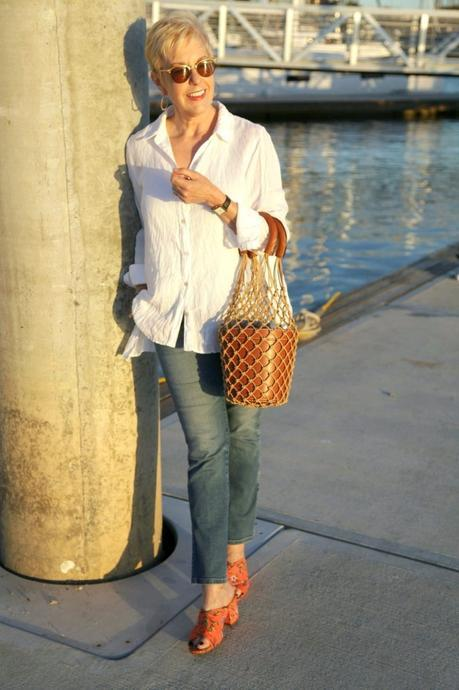 style blogger Susan B. wears an easy white shirt in linen with jeans, a bucket bag and slide sandals. Details at une femme d'un certain âge.