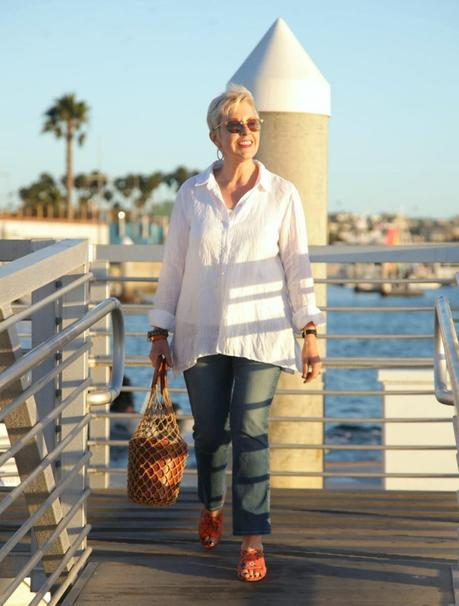 style blogger Susan B wears an easy white shirt with jeans, a Staud bucket bag and orange sandals. Details at une femme d'un certain age.