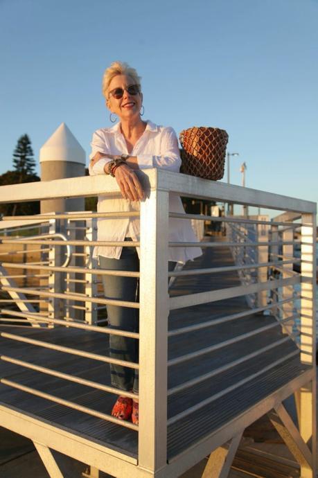 style blogger Susan B. wears a white linen shirt, orange Sam Edelman sandals