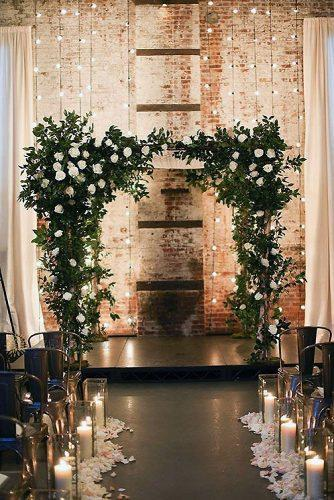 wedding light beautiful wedding arch with lights in the background and tall candles along the aisle alison conklin