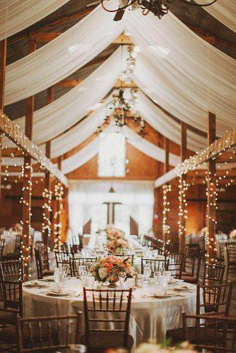rustic wedding reception decorated with a white cloth to the wedding reception barn on the ceiling elegant chandeliers on wooden beams glowing light bulbs nessa k photography