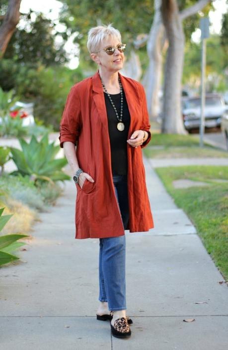 style blogger Susan B. wears a copper lightweight jacket from Eileen Fisher, jeans, and leopard mules.