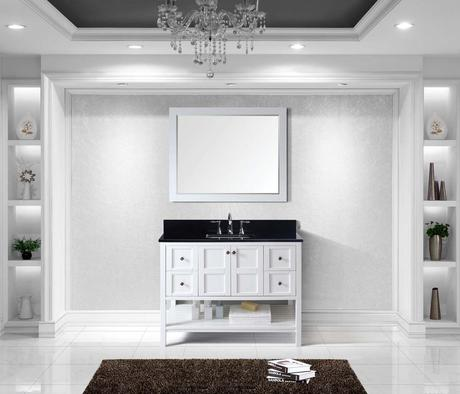 A beautiful transitional white vanity with a striking black top