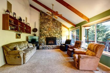 living room with fireplace and stone wall
