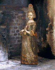 An early eighteenth century dummy board from the Great Chamber at Trerice, depicting a girl holding a basket of flowers.