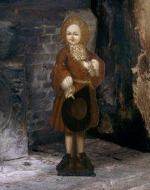 An early eighteenth century painted dummy board from the Great Chamber at Trerice, depicting a boy holding a hat.