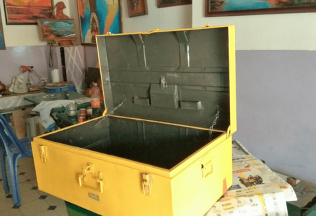 The box painted yellow with the handle, hinges, locks and latch painted orange